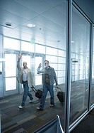 Travelers with suitcases waving in airport