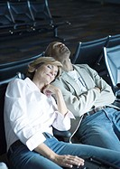 Travelers sleeping in airport lounge