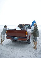Young adults standing around pick-up truck on beach