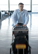 Man pushing luggage cart in airport