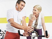 Woman sitting on exercise bike man checking control panel