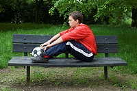Young man on a bench with a football