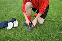 Footballer putting boots on