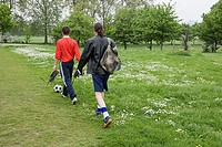 Two young men walking in park