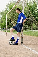 Footballer leaning on goalpost
