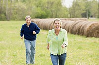 Mature couple running in field