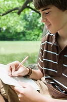 Boy writing in a notebook (thumbnail)