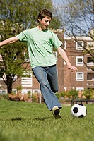 Teenager kicking football