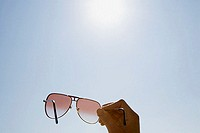 Person holding sunglasses (thumbnail)