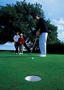 low angle view of a golfer hitting the ball towards the hole