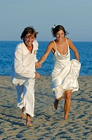Newly young married couple running on the beach