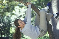Young woman climbs on a brench of a tree