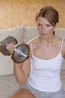 A blonde woman working out as she holds a dumbbell in her hand.