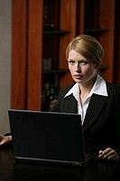 A blonde businesswoman with a laptop.