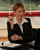 A blonde businesswoman with a laptop and a planner beside her.