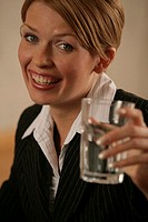 A blonde businesswoman holds a glass of water as she smiles at the camera.