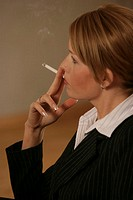 A blonde businesswoman smoking.