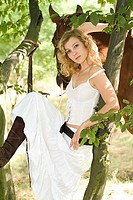 A beautiful woman in modern white clothes poses against the trunk of the tree.