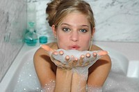 Woman taking bubble bath, blowing on foam