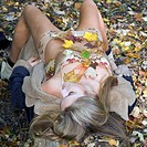 Young woman lying on autumn leaves, outdoors, elevated view