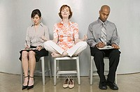 Woman Meditating Between Two Job Applicants