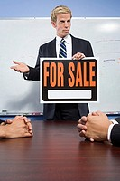 Businessman holding for sale sign