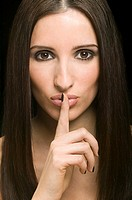 Beautiful woman with finger to mouth