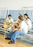 Group of teens sitting with basketball on bleachers in school gym