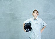 Boy standing with helmet under arm