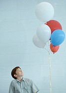 Boy looking up at bunch of balloons