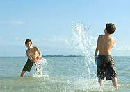 Two boys splashing in water at beach