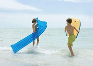 Children running in surf at beach, with raft and body board