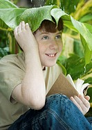 Boy with book sitting under leaf in rain