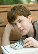 Boy with calculator and school book