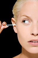 Woman putting cotton bud in her ear
