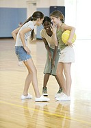 Three teen girls huddling in school gym