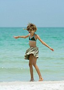 Girl standing in wind on beach
