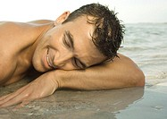 Man lying on wet sand