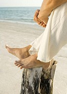 Man sitting on beach with feet on wooden post, low section