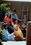 Two couples relaxing outdoors with dog.