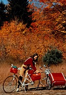 Woman preparing for bicycle camping trip by packing bicycle pouches outdoors with fall foliage.