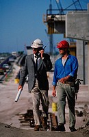 Foreman on cellular phone with blueprints walks with construction worker on construction site.