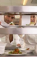 Male and female cooks checking orders on counter, view through shelves