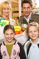 Parents and children (8-10) by supermarket checkout, smiling, portrait