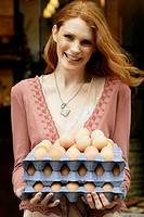 Young woman holding trays of eggs, smiling, portrait