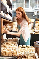 Young woman in shop looking at selection of cheeses