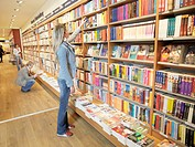 Young woman selecting book from shelf in book shop