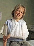 Boy (6-8) sitting on hospital bed with arm in sling, smiling, portrait