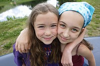 Two girls (10-12) with arms around each other, portrait, close-up