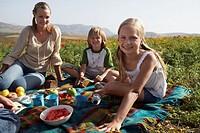 Family having picnic, mother and children (9-11) smiling, portrait